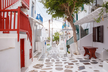 santorini greece: Mykonos town streetview with tree and red banisters, Mykonos town, Greece