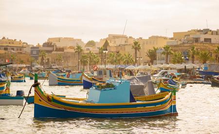 Traditional Luzzu fishing boats at Marsaxlokk Market at morning - Malta