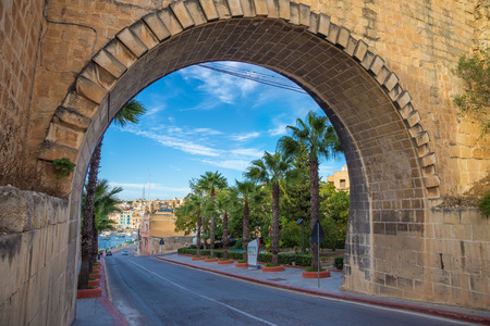 Maltese arch with palm trees and blue sky - Valletta, Malta