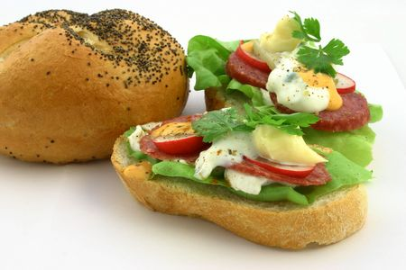 Close up at small sandwiches with various ingredients next to breadroll photo