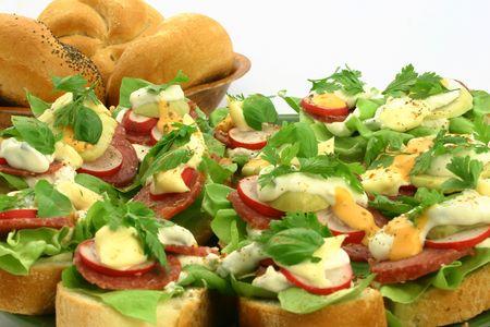 raddish: Delicious sandwiches with salami, raddish, basil and sauces next to breadrolls