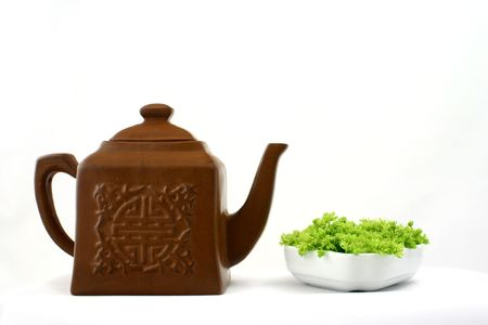 Small square brown teapot witch chinese pattern opposite to green flowers put in white porcelain Stock Photo - 664637