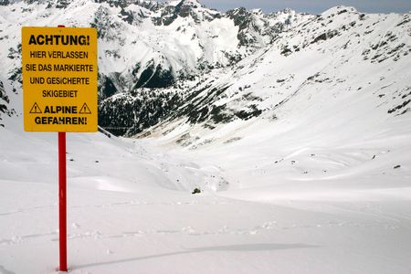 alpine zone: Warning about leaving marked and protected piste against a mountain background.