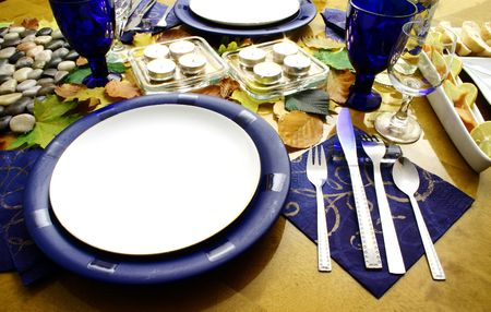 Table covered with autumn leaves and setting plates photo