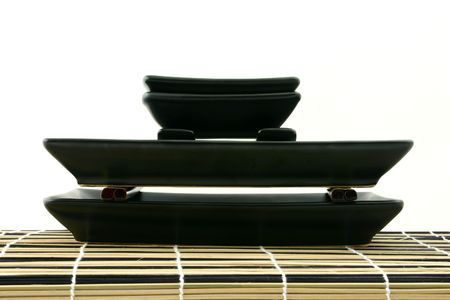 Sushi dishes put on each other laying on mat (perpendicular view) photo