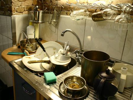 Lots of dirty plates, pots and tableware ready to wash photo