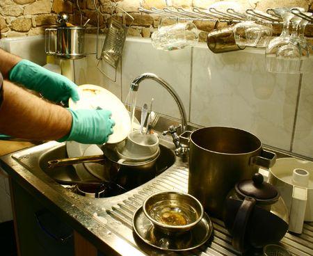 manos sucias: Lavando platos con guantes en la peque�a cocina  Foto de archivo