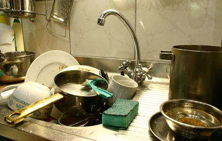dirty dishes: Dirty dishes in the kitchens sink ready to start washing Stock Photo