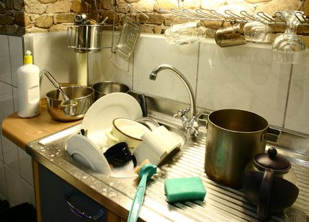 dirty dishes: Lots of dirty dishes in small kitchens sink