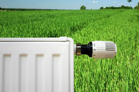 Radiator with thermostat set optimal on a young green grain photo