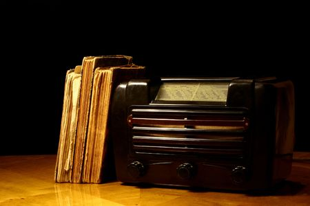 Vintage radio and old books standing together on a table photo
