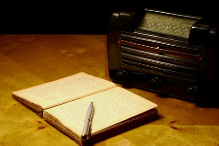 View at old book with pen together with retro radio set photo