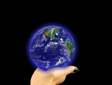 macrocosm: glowing blue globe lying on a womans hand on a black background. Image of earth used under Terms and Conditions of Nasa http:visibleearth.nasa.gov