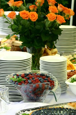 catering table: View at catering table with fruits, flowers and pile of clean plates Stock Photo