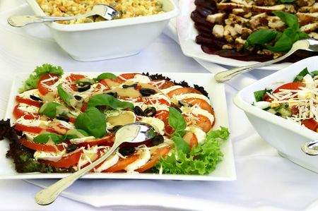 catering table: Close up at delicious platters of salads with spoon