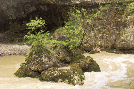 rushing water: Small stone islet in the rushing water of a mountain stream.Chegem gorge.The North Caucasus.