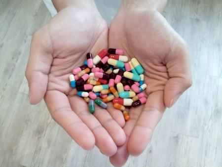 colorful: Hands with a variety of pills.