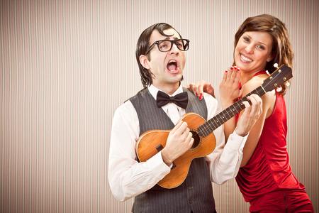 mujer fea: hombre novio empollón en el amor con una mujer hermosa reproducir una canción serenata con el ukulele para el Día de San Valentín