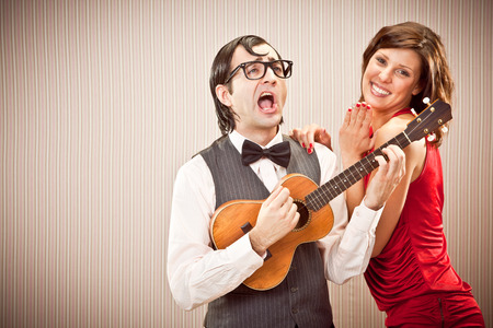 ugly man: nerd boyfriend man in love with beautiful woman play a serenade song with ukulele for Valentine Day