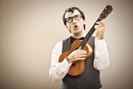 nerd: Nerd man with glasses play ukulele