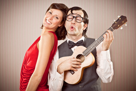 serenade: nerd boyfriend man in love with beautiful woman play a serenade song with ukulele for Valentine Day