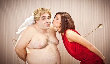 cupid: surprised shy cupid kiss by beautiful love woman for valentine day