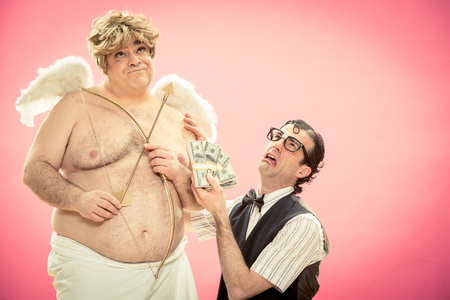 cupid man: Desperate man with nerd glasses deal love bow and arrow with money from cupid for valentine day