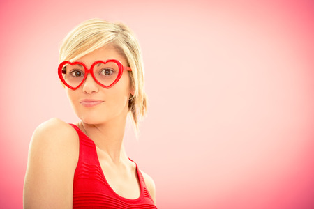 Young beautiful woman with hearth shaped glasses in red dress smile on pink for valentine day