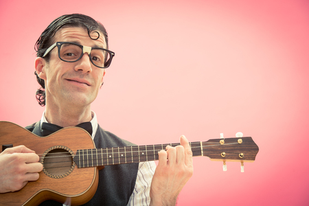maldestro: Happy nerd man with glasses play music with ukulele guitar