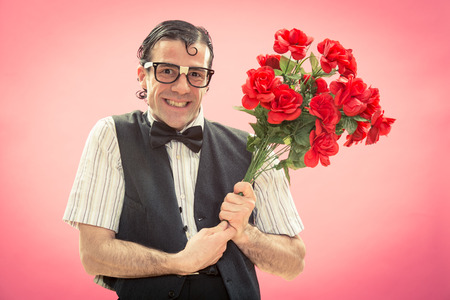 Shy nerdy man with glasses give red roses flower bunch on pink for valentine day Stock Photo