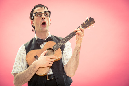 Nerd man with glasses play music with ukulele guitar Imagens