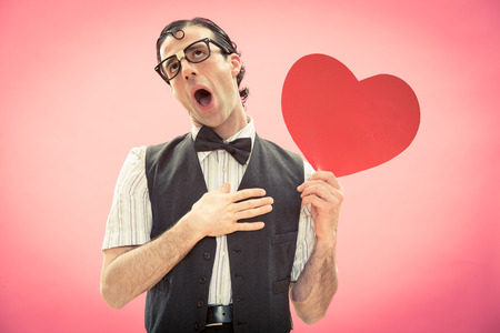 Nerd man with glasses surprised by love heart on pink for valentine day
