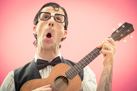 Nerd man with glasses play music with ukulele guitar Stock Photo