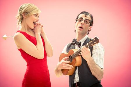 彼は得るオタク男彼氏女性愛のキューピッド矢印とバレンタインデーのウクレレ ギターで曲を再生