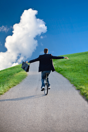 blu sky: businessman riding unicycle in countryside with blu sky and clouds