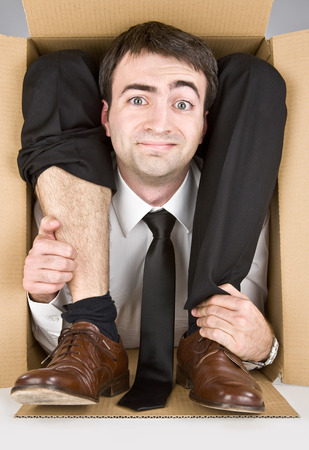 contortionist: flexible businessman with doubtful smiling face in a cardboard box