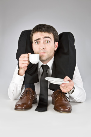 contortionist: flexible businessman with doubtful face isolated on white drinking coffee Stock Photo