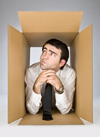 contortionist: flexible businessman with doubtful face in a cardboard box
