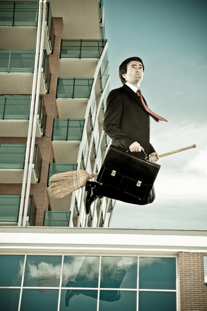 Businessman fly with his broom in a urban landscape