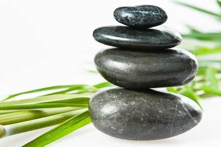 hot rock therapy: spa stone pebbles stack isolated on white with bamboo