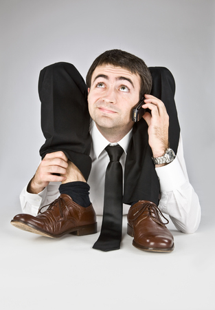 contortionist: flexible businessman with doubtful face isolated on white talking on the phone