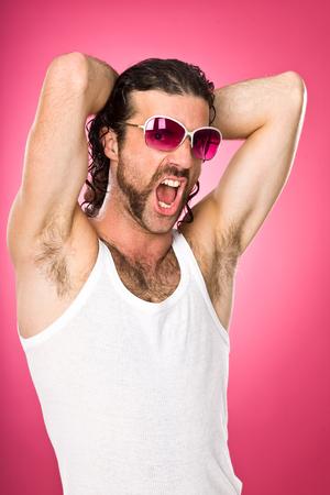 ピンクに分離された眼鏡の面白いマッチョな男