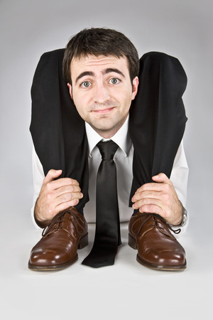flexibele zakenman met dubieuze gezicht geïsoleerd op wit Stockfoto