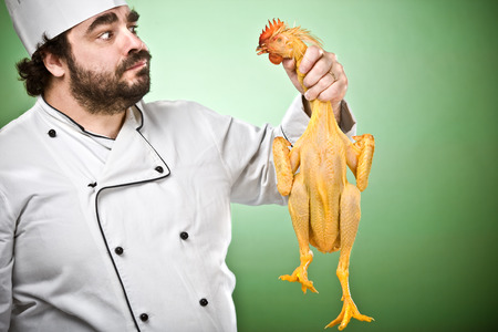 doubtful: doubtful chef cook and show chicken isolated on green Stock Photo