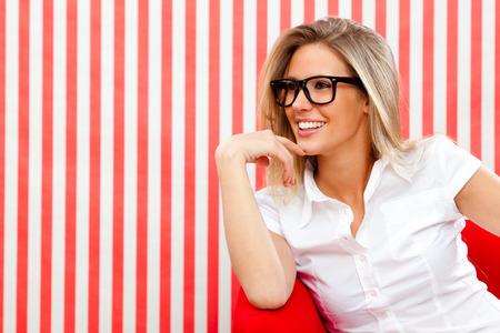 赤のテクスチャ背景にメガネで官能的なブロンドの女の子をピンで留める