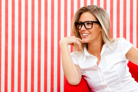 pin up sensuele blond meisje met een bril op rode textuur achtergrond