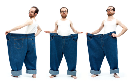 large: funny slim man with large pants jeans isolated on white