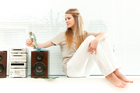 rom: Young beautiful woman listen music with cd rom in a living room