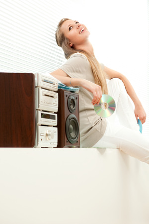 cd rom: Young beautiful woman listen music with cd rom in a living room