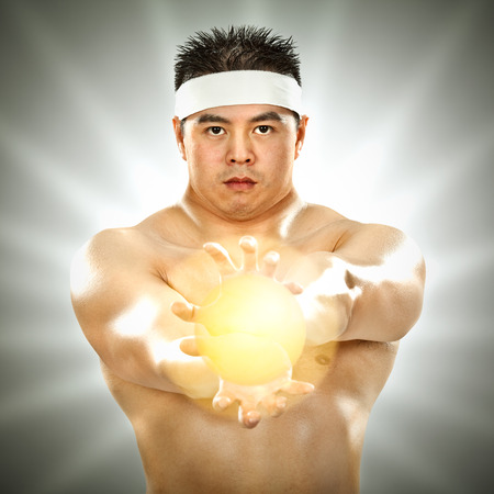 asian body builder with energy in his hands on grey background Banco de Imagens